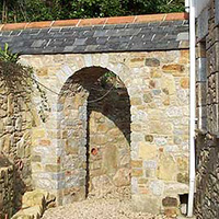 Retaining garden wall with a granite set arch